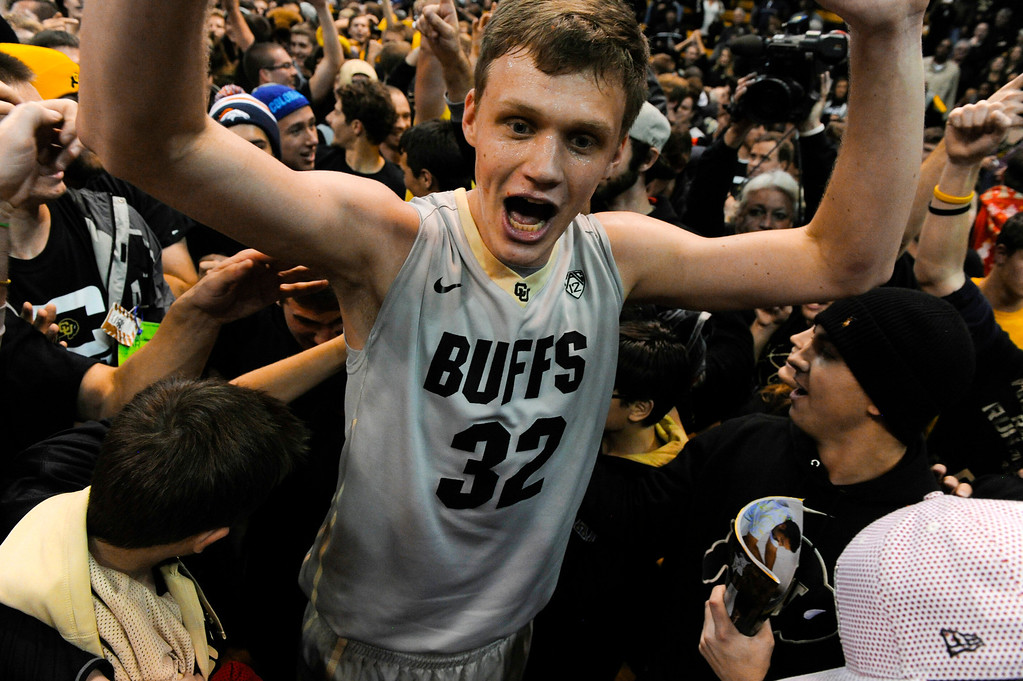 . Colorado University center, Ben Mills makes his way through a sea of fans after CU defeated Kansas at the buzzer 75-72 at the Coors Events Center in Boulder Colorado Saturday afternoon, December 07, 2013. (Photo By Andy Cross/The Denver Post)