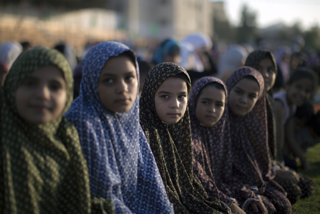 . Palestinian girls take part in the morning Eid al-Fitr prayer in Gaza City on August 8, 2013. Muslims worldwide observe the Eid al-Fitr prayer to mark the end of the fasting month of Ramadan and the beginning of the new month of blessing Shawwal 1434 Hijriah. MAHMUD HAMS/AFP/Getty Images