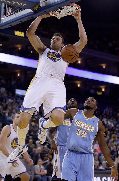 . Andrew Bogut #12 of the Golden State Warriors dunks the ball over Kenneth Faried #35 of the Denver Nuggets at ORACLE Arena on January 15, 2014 in Oakland, California.  (Photo by Ezra Shaw/Getty Images)