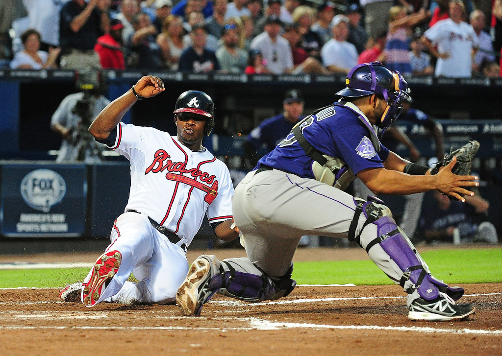 . Justin Upton #8 of the Atlanta Braves scores a fourth inning run against Wilin Rosario #20 of the Colorado Rockies at Turner Field on July 30, 2013 in Atlanta, Georgia. (Photo by Scott Cunningham/Getty Images)