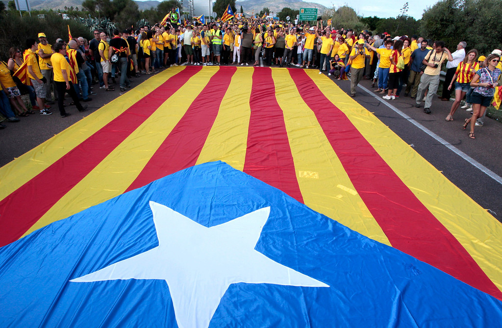 . Catalans react as they surround a giant Independentist Catalan flag (Senyara), as part of a campaign for independence from Spain during Catalonia National Day, or Diada, in Alcanar, on September 11, 2013. Independence-seeking Catalans  marshalled their forces today to make a human link they say will stretch across 86 cities, towns and villages along the coast of the northeastern region on the Mediterranean, passing landmarks such as the Sagrada Familia basilica in Barcelona and the city\'s Camp Nou football stadium. JOSE JORDAN/AFP/Getty Images