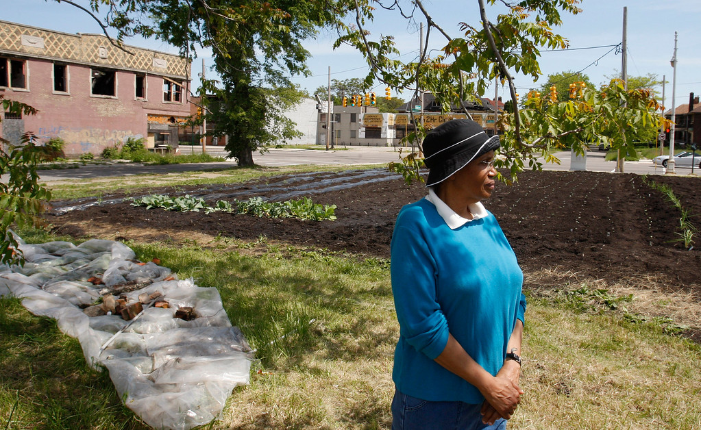 . In this Thursday, May 20, 2010 photo, Rose Stallard stands next to a neighborhood garden in Detroit,  where she volunteers. She\'s lived in the neighborhood since 1952, when homes and apartments stood on land that this year will produce rows of greens, tomatoes and peppers. (AP Photo/Carlos Osorio)