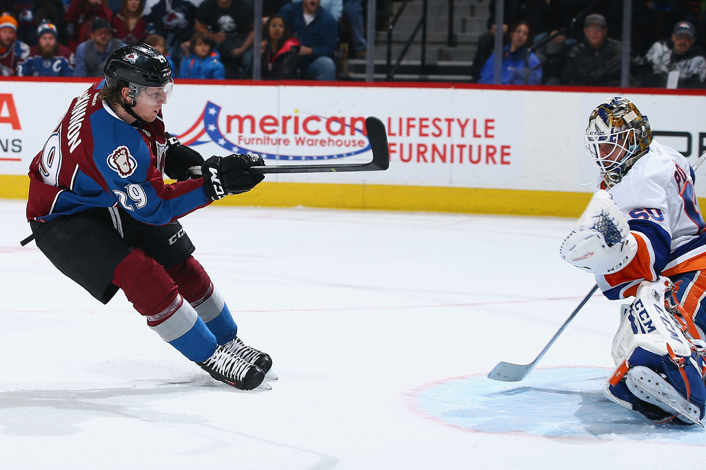. DENVER, CO - JANUARY 10:  Nathan MacKinnon #29 of the Colorado Avalanche gets the puck past goalie Kevin Poulin #60 of the New York Islanders for a second period goal to give the Avalanche a 1-0 lead at Pepsi Center on January 10, 2014 in Denver, Colorado.  (Photo by Doug Pensinger/Getty Images)
