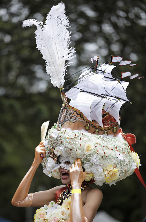 . A parade participant wears an elaborate headpiece during Mardi Gras in Sydney, Australia, Saturday, March 2, 2013. 10,000 are marching along side 115 floats in the annual parade that celebrates lesbian and gay pride. (AP Photo/Rick Rycroft)