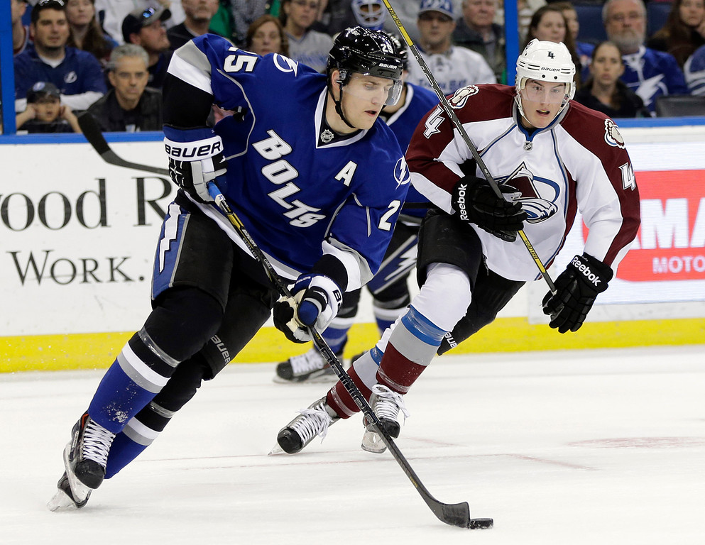 . Tampa Bay Lightning defenseman Matt Carle (25) carries the puck past Colorado Avalanche defenseman Tyson Barrie (4) during the first period of an NHL hockey game Saturday, Jan. 25, 2014, in Tampa, Fla. (AP Photo/Chris O\'Meara)