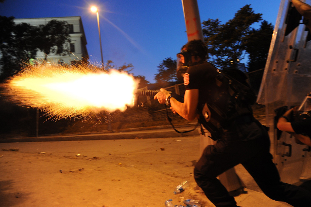 . Turkish riot police officer fires tear gas during clashes with protestors between Taksim and Besiktas in Istanbul on June 3, 2013 during a demonstration against the demolition of the park. Turkish police on June 1 began pulling out of Istanbul\'s iconic Taksim Square, after a second day of violent clashes between protesters and police over a controversial development project. Thousands of demonstrators flooded the site as police lifted the barricades around the park and began withdrawing from the square. What started as an outcry against a local development project has snowballed into widespread anger against what critics say is the government\'s increasingly conservative and authoritarian agenda. AFP PHOTO/BULENT  KILIC/AFP/Getty Images