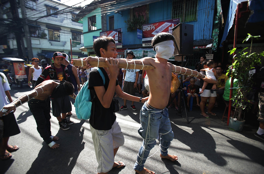 . Filipino penitents with wooden stakes are tied to their arms as they walk along the street during Maundy Thursday rituals to atone for sins on March 28, 2013 in suburban Mandaluyong, east of Manila, Philippines. The ritual is frowned upon by church leaders in this predominantly Roman Catholic country. (AP Photo/Aaron Favila)