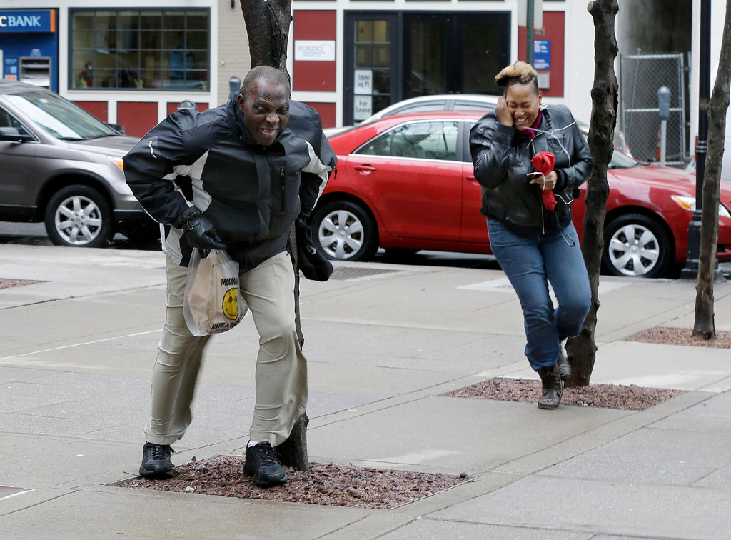 . A man braces against a small tree and a woman leans against the wind as it whips between buildings Wednesday, March 6, 2013, in Trenton, N.J. Winds from a winter storm are lashing New Jersey  and are doing some damage. The National Weather Service says rain was expected to change to all snow toward Wednesday night.   (AP Photo/Mel Evans)
