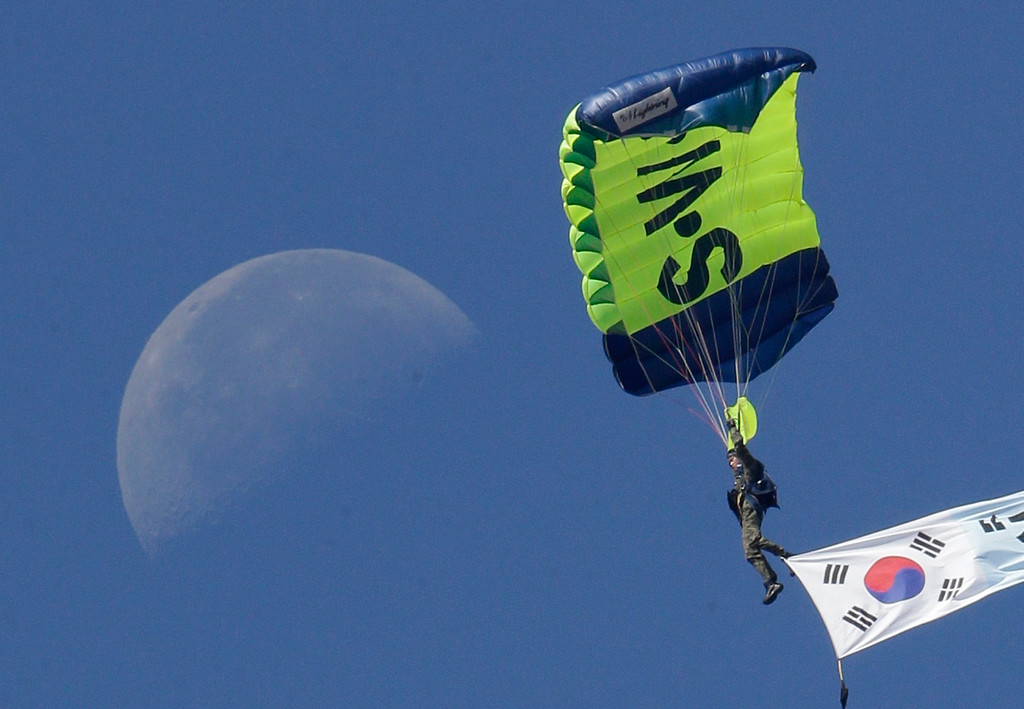 . A South Korean Special Army soldier parachutes with the country\'s national flag as the moon is seen in the sky during the media day for the 65th anniversary of Armed Forces Day at Seoul military airport in Seongnam, South Korea, Friday, Sept. 27, 2013.  (AP Photo/Lee Jin-man)