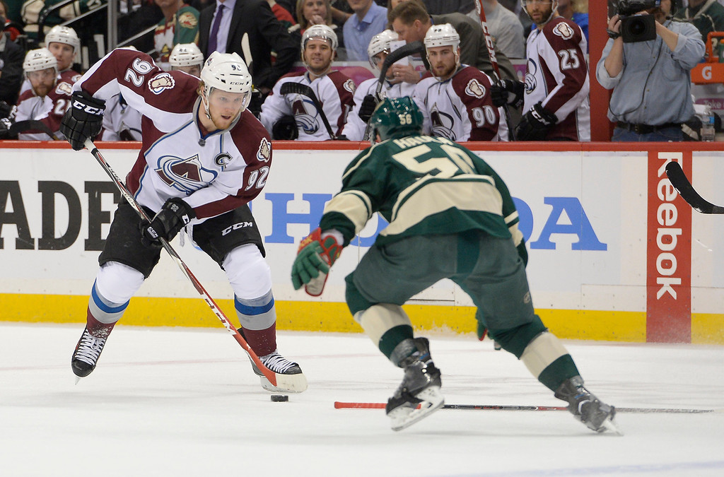 . Colorado Avalanche left wing Gabriel Landeskog (92) dated the puck in to the Minnesota Wild zone as Minnesota Wild left wing Erik Haula (56) comes in on defense during the first period April 24, 2014 at Xcel Energy Center. (Photo by John Leyba/The Denver Post)