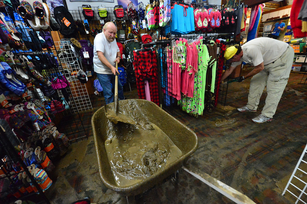 . Friends and volunteers help clear mud from Outdoor World on Saturday, Sept 14, 2013. Many businesses along Elkhorn Avenue found mud covering their floors when they got to the stores. Walt Hester/Estes Park Trail-Gazette