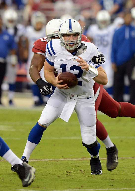 . Andrew Luck #12 of the Indianapolis Colts avoids being sacked by Calais Campbell #93 of the Arizona Cardinals at University of Phoenix Stadium on November 24, 2013 in Glendale, Arizona.  (Photo by Norm Hall/Getty Images)