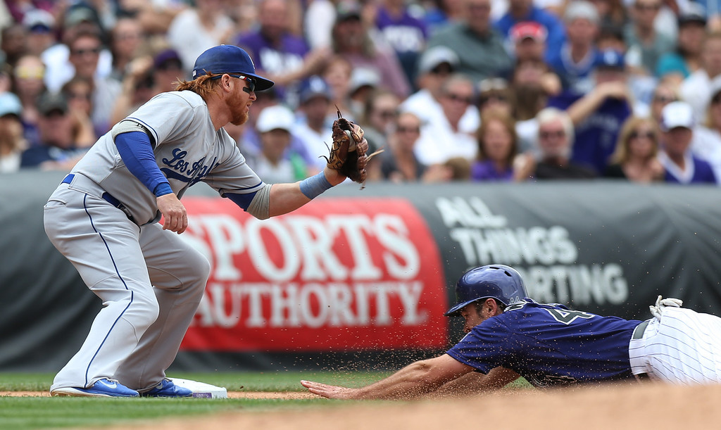 . Los Angeles Dodgers third baseman Justin Turner, left, fields the throw as Colorado Rockies\' Ryan Wheeler slides safely into third base in the fifth inning of a baseball game in Denver on Saturday, June 7, 2014. (AP Photo/David Zalubowski)