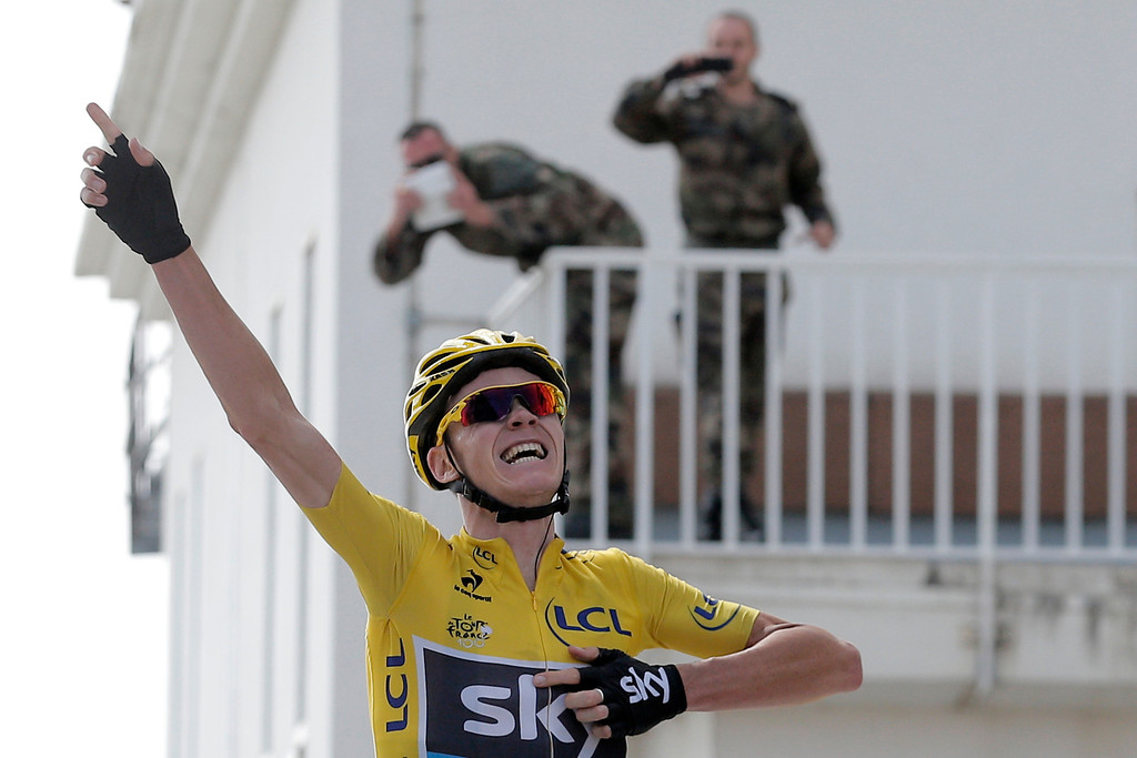 . French soldiers take images as stage winner and overall leader Christopher Froome of Britain celebrates as he crosses the finish line of the fifteenth stage of the Tour de France cycling race over 242.5 kilometers (150.7 miles) with start in in Givors and finish on the summit of Mont Ventoux pass, France, Sunday July 14, 2013. The riders will climb to an altitude of 1912 meters (6,273 Feet) as they tackle Mont Ventoux pass at the end of the longest stage of the 100th Tour de France edition. (AP Photo/Christophe Ena)