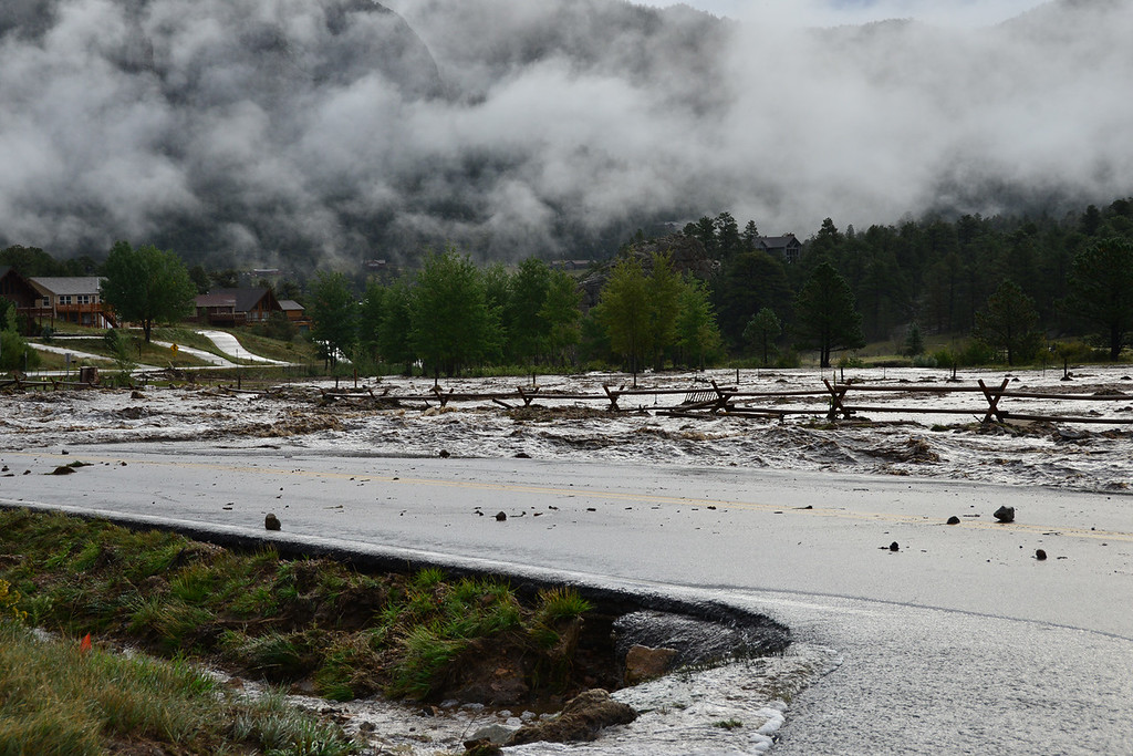 . Low hanging clouds create a surreal scene Friday morning, Sept. 13, 2013 as floodwater from Fish Creek carry debris. John Cordsen/Estes Park Trail-Gazette