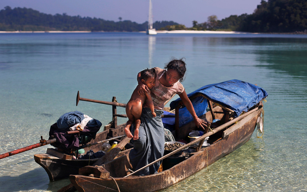 . In this Sunday, Feb. 9, 2014 photo, a woman belonging to Moken tribe, nomads of the sea, carries her child as she steps out of her canoe on Island 115 in Mergui Archipelago, Myanmar. Isolated for decades by the country�s former military regime and piracy, the Mergui archipelago is thought by scientists to harbor some of the world�s most important marine biodiversity and looms as a lodestone for those eager to experience one of Asia�s last tourism frontiers before, as many fear, it succumbs to the ravages that have befallen many of the continent�s once pristine seascapes. Although no accurate census is available, about 2,000 Moken are believed to inhabit the archipelago, significantly reduced through migration, intermarriage with Burmese and deaths of males from rampant alcohol and drug abuse.  (AP Photo/Altaf Qadri)