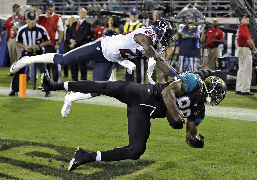 . Jacksonville Jaguars tight end Marcedes Lewis (89) pulls in a one-yard touchdown reception in front of Houston Texans cornerback Kareem Jackson (25) during the first quarter of an NFL football game Thursday, Dec. 5, 2013, in Jacksonville, Fla. (AP Photo/Chris O\'Meara)