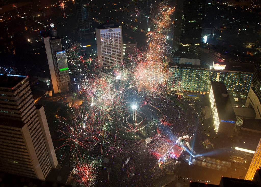 . Fireworks explode as thousands of people line the streets of downtown Jakarta to welcome in the New Year in Indonesia, Wednesday, Jan. 1, 2014. (AP Photo/Mark Baker)