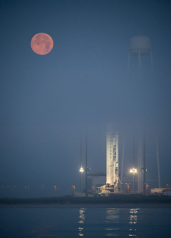 . This photo provided by NASA, the full Moon sets in the fog behind the Orbital Sciences Corporation Antares rocket with a Cygnus spacecraft onboard at the launch pad on Saturday, July 12, 2014, at NASA\'s Wallops Flight Facility, Va.  The Antares will launch with the Cygnus spacecraft filled with over 3,000 pounds of supplies for the International Space Station.  (AP Photo/NASA, Bill Ingalls)