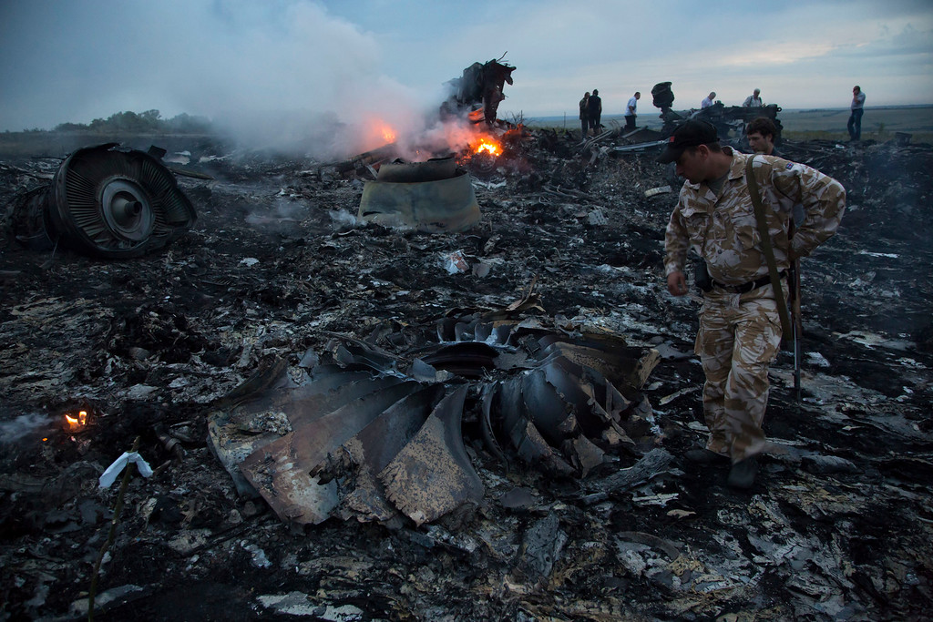 . People walk amongst the debris at the crash site of a passenger plane near the village of Grabovo, Ukraine, Thursday, July 17, 2014. Ukraine said a passenger plane carrying 295 people was shot down Thursday as it flew over the country, and both the government and the pro-Russia separatists fighting in the region denied any responsibility for downing the plane. (AP Photo/Dmitry Lovetsky)