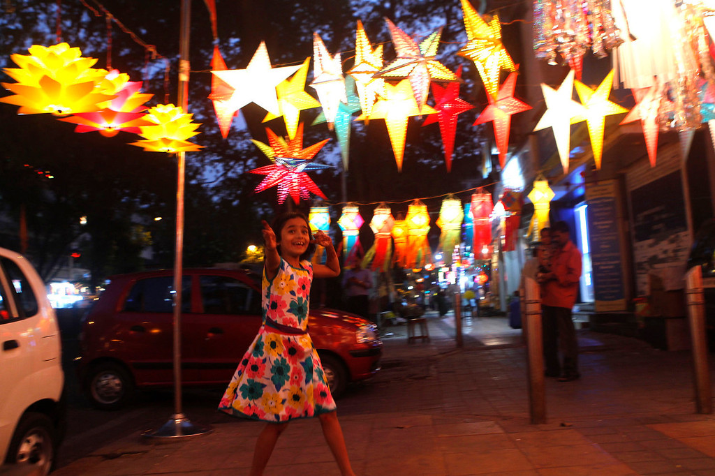 . An Indian girl walks past lanterns hung on roadside stalls on the eve of Diwali festival in Mumbai, India, Saturday, Nov. 2, 2013. Hindus light up their homes and pray to Lakshmi, the goddess of wealth, during the festival which will be celebrated on Nov. 3. (AP Photo/Rajanish Kakade)