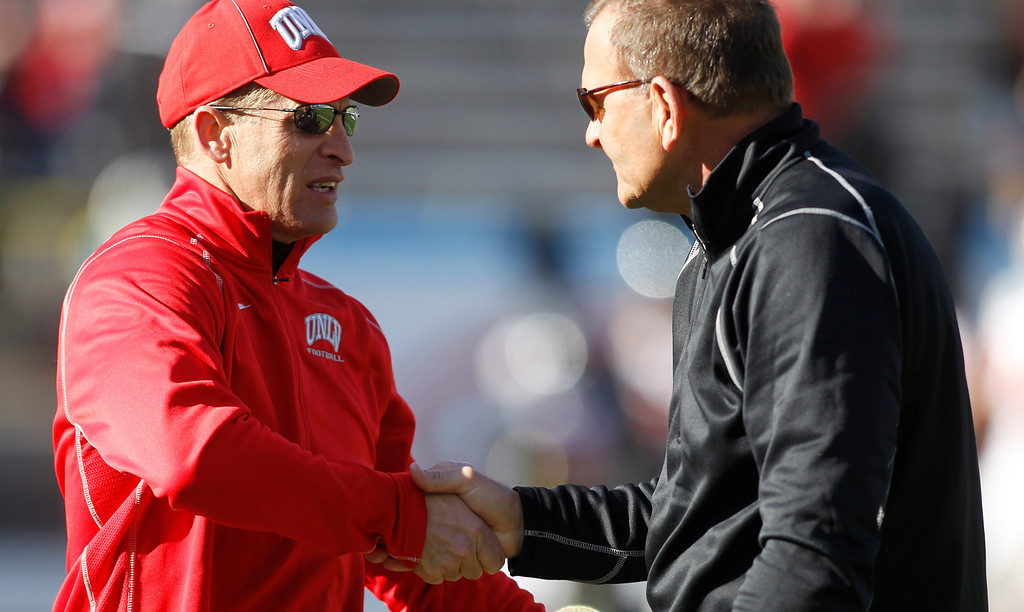 . UNLV head coach Bobby Hauck, on left, shakes hands with North Texas head coach Dan McCarney before the start of the Heart of Dallas NCAA college football game, Wednesday, Jan. 1, 2014, in Dallas. (AP Photo/Mike Stone)