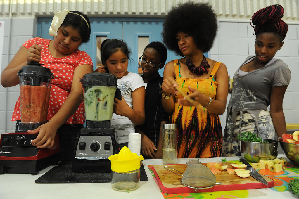 """. DENVER, CO - JULY 1:  Neambe Leadon Vita, second from right, helps summer camp students make juice from fresh local produce that includes cucumbers, strawberries, limes, watermelon, apples, coconut water and baby kale during a summer camp at St. Charles Recreation Center at 3777 Lafayette Street in Denver, CO. on July 1, 2013.  The kids are from left to right:  Kelly Garcia, 9, Caren Alvarado, 12, Dashawn Tolbert, 13, and Letencia Blake, 14, far right.   DJ Cavem Moetavation, not shown, and his wife Neambe Leadon Vita hold the camp to introduce kids to healthy eating habits, teach them about organic farming and changing the way they think about food. They also make organic juice during the day using produce from the couple\'s garden which includes cucumbers, strawberries, watermelon, kale, lime and coconut water.   As part of our \""""Summer of Love\"""" series for the Style section we profile the relationship of DJ Cavem Moetavation (a.k.a. Ietef Vita) and his wife Neambe Vita.  They are proud and longtime Five Points residents. They\'re artists, community activists, musicians, teachers and more.  They espouse the idea of being vegan or vegetarian and promote eating healthfully and organically.  (Photo by Helen H. Richardson/The Denver Post)"""