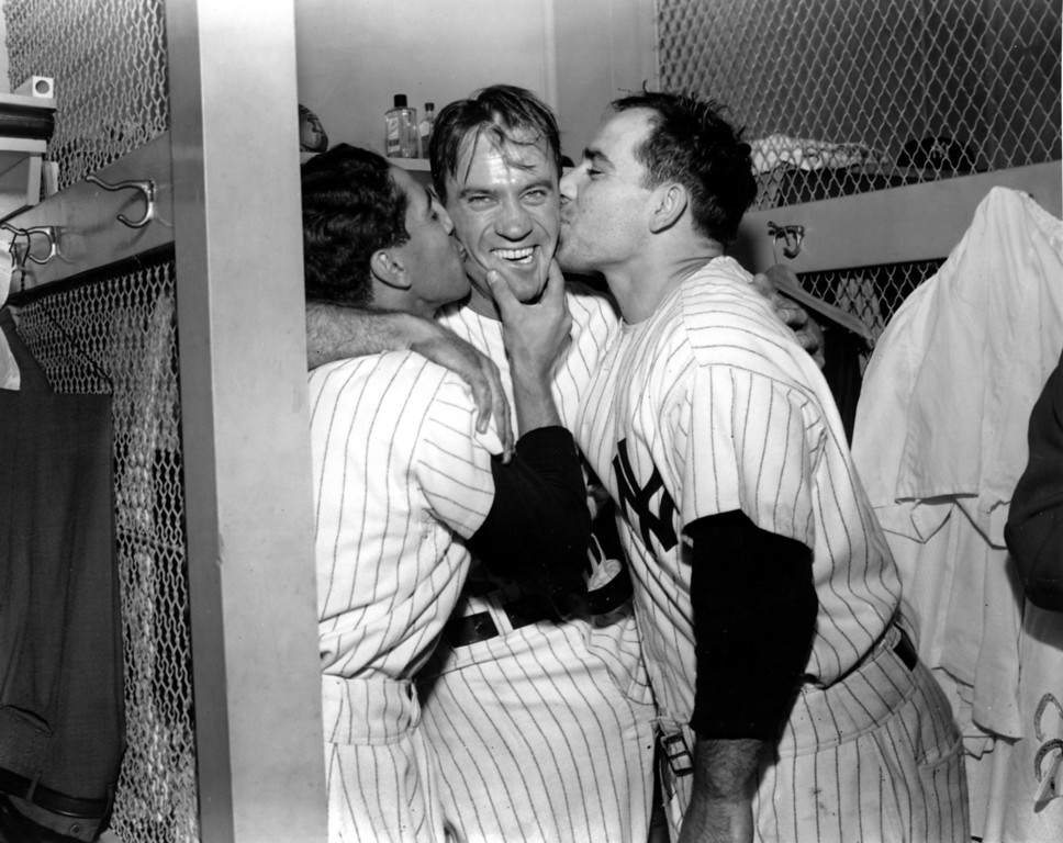 . New York Yankees right fileder Hank Bauer, center, is kissed by shortstop Phil Rizzuto, left, and catcher Yogi Berra in the dressing room after winning the sixth and deciding game of the World Series at Yankee Stadium in New York City, Oct. 10, 1951.  Bauer\'s bases-loaded triple in the sixth inning gave the Yankees a 4-3 win over the New York Giants.  Bauer also made the game-ending catch of pinch-hitter Sal Yvar\'s low line drive with the Giants\' tying run on base.  (AP Photo)