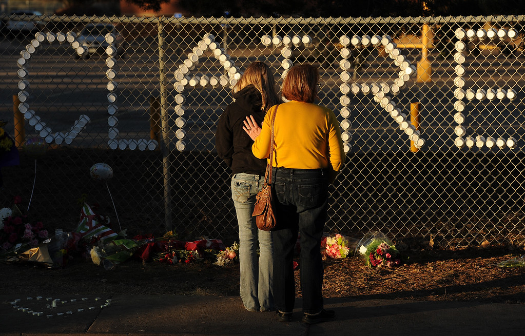 . Arapahoe High School senior Melissa Tombaugh, 18, left, is comforted by her mother Jeannette, right, at a tribute set up for shooting victim Claire Davis along Dry Creek road near Arapahoe High School in Centennial, CO on December 15, 2013. Students from the high school attended a prayer service to pray for the recovery of Davis who was shot during the recent shooting at the high school.  (Photo By Helen H. Richardson/ The Denver Post)