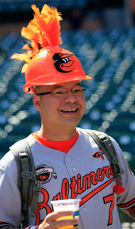. A Baltimore Orioles fan watches the team warm up before the start of the Orioles and Boston Red Sox Opening Day game at Oriole Park at Camden Yards on March 31, 2014 in Baltimore, Maryland.  (Photo by Rob Carr/Getty Images)
