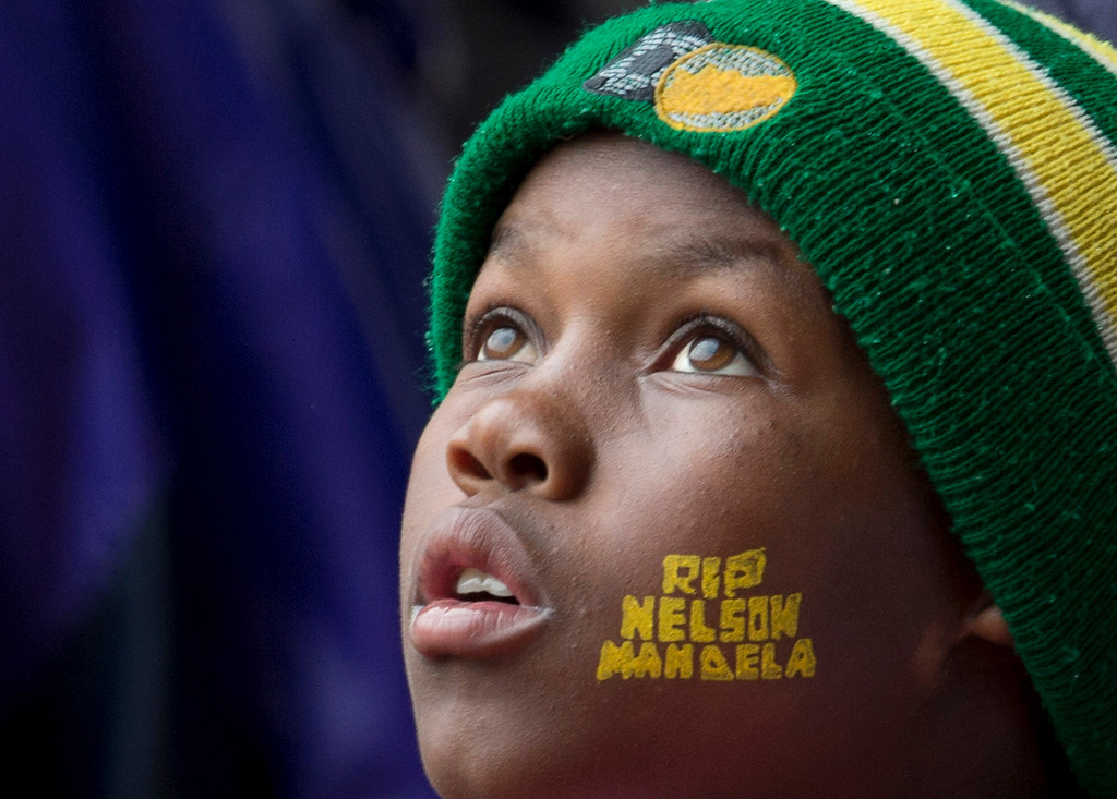 """. A boy with \""""Rest In Peace Nelson Mandela\"""" painted on his face looks up to the skies during the memorial service for former South African president Nelson Mandela at the FNB Stadium in Soweto, near Johannesburg, South Africa, Tuesday Dec. 10, 2013. (AP Photo/Peter Dejong)"""