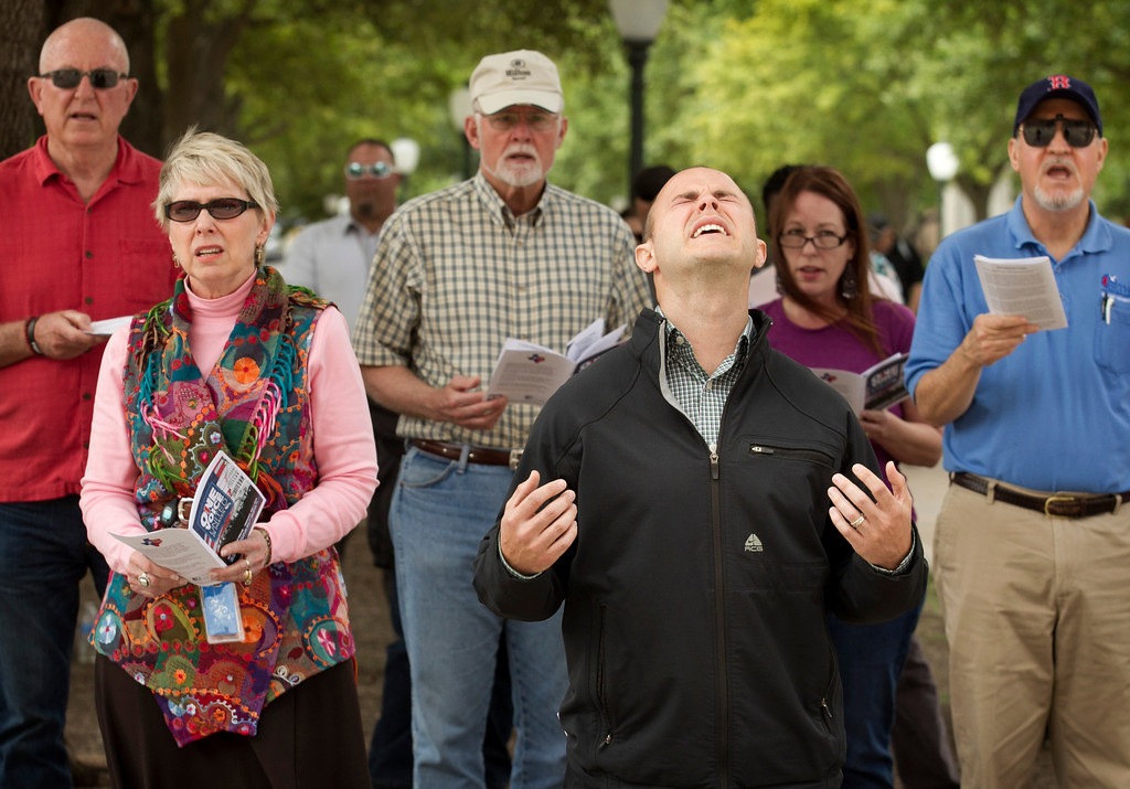 . Shane Simms, right, sings during the One Voice United in Prayer event at the Capitol in Austin, Texas, on Thursday, May 1, 2014.  About 100 people gathered at the Capitol on the 63rd Annual National Day of Prayer to sing praise songs and pray for the church, families, the military, education, the government, business and the media. (AP Photo/Austin American-Statesman, Jay Janner)