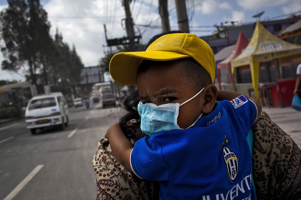 . A boy waring a mask is carried through through an area covered by ash after Mount Sinabung erupted spewing volcanic materials at Berastagi village on November 25, 2013 in Karo district, North Sumatra, Indonesia. (Photo by Ulet Ifansasti/Getty Images)