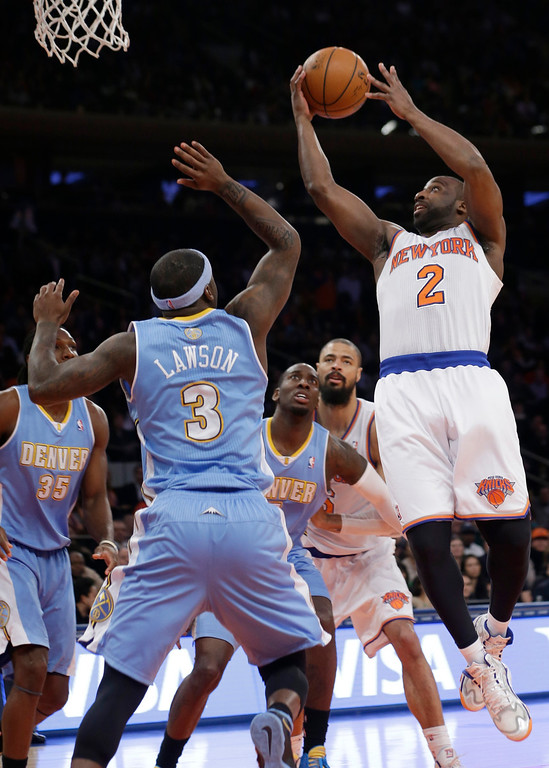 . New York Knicks\' Raymond Felton (2) jumps next to Denver Nuggets\' Ty Lawson (3) during the first half of an NBA basketball game Friday, Feb. 7, 2014, in New York. (AP Photo/Frank Franklin II)