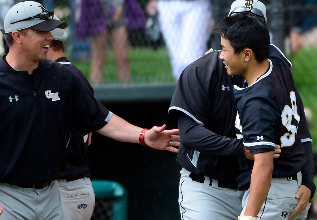 . LAKEWOOD, CO - MAY 23: Coachs congratulate  Justin Akiyama, right, after he made the game-winning hit in the 7th inning to win the game for Green Mountain. The Durango Demons take on the Green Mountain Rams in the 4A Baseball State Semi-Final Championships. (Kathryn Scott Osler, The Denver Post)