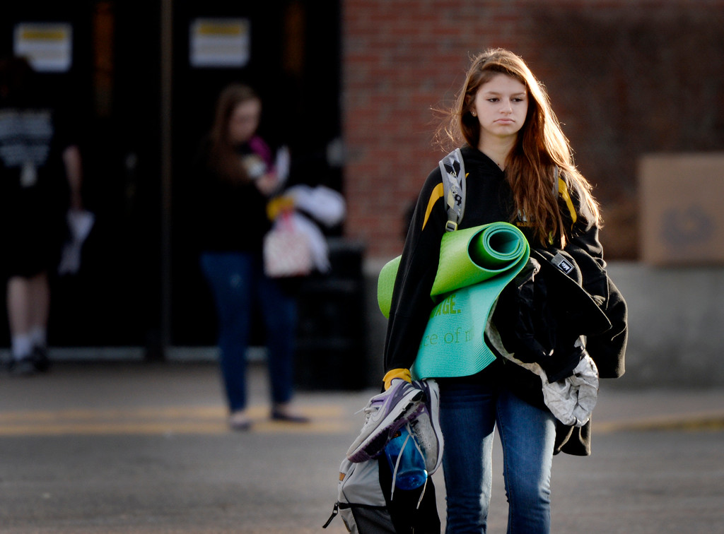 . A student carries her belongings through a parking lot at Arapahoe High School in Centennial, CO December 19, 2013. Seniors and Juniors returned  to the school for two hour periods Thursday, Sophomores and Freshmen will return on Friday.  (Photo By Craig F. Walker / The Denver Post)