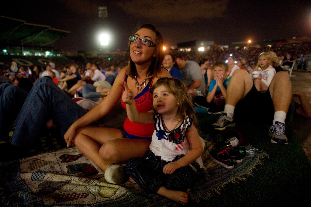 . DENVER - JULY 4: Maddie Golembiewski and her daughter Zoey, 3, watch the Independence Day fireworks show after an MLS soccer match between the Colorado Rapids and the New York Red Bulls on July 4, 2013 at Dick\'s Sporting Goods Park. The Rapids defeated the Red Bulls 2-0. (Photo By Grant Hindsley / The Denver Post)