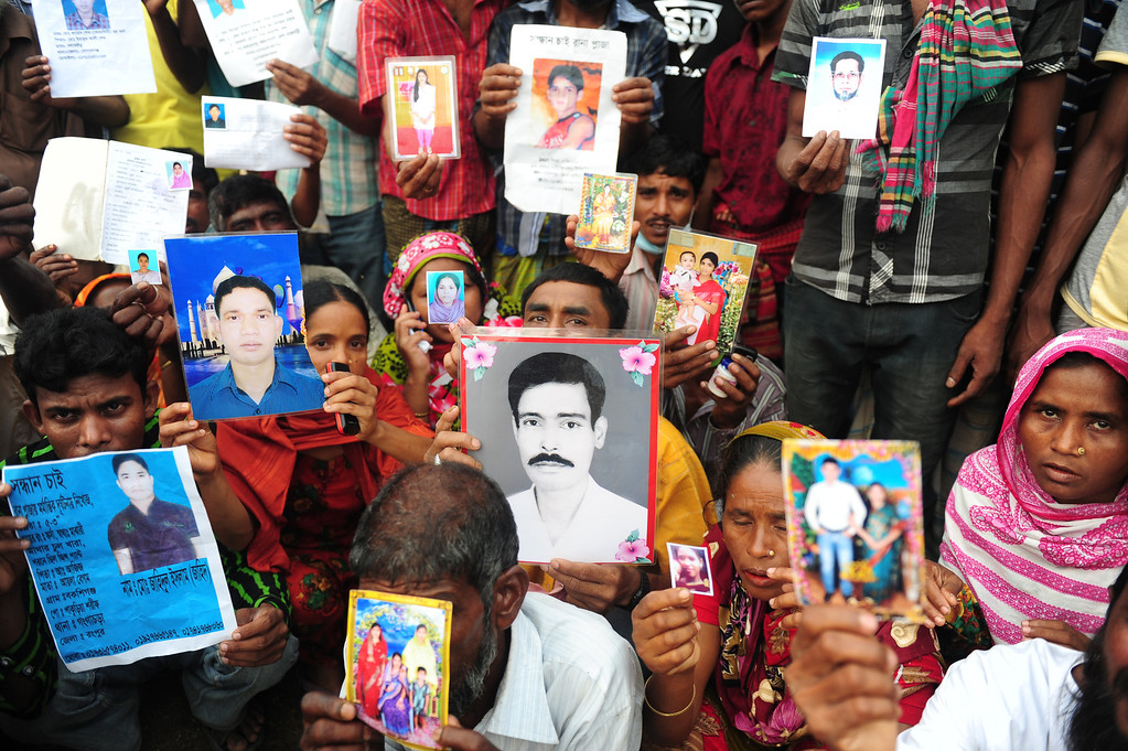 . Bangladeshi relatives hold photos of the missing and dead workers three days after an eight-storey building collapsed  in Savar, on the outskirts of Dhaka on April 27, 2013. Police arrested two textile bosses over a Bangladeshi factory disaster as the death toll climbed to 332 and distraught relatives lashed out at rescuers trying to detect signs of life. MUNIR UZ ZAMAN/AFP/Getty Images