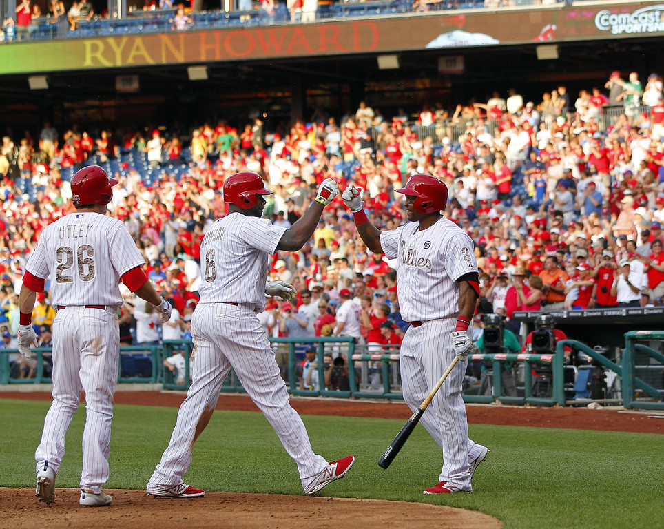 . Ryan Howard #6 of the Philadelphia Phillies is congratulated by teammates Chase Utley #26 and Marlon Byrd #3 after his two-run home run against the Colorado Rockies during the sixth inning in a game at Citizens Bank Park on May 26, 2014 in Philadelphia, Pennsylvania. The Phillies defeated the Rockies 9-0. (Photo by Rich Schultz/Getty Images)