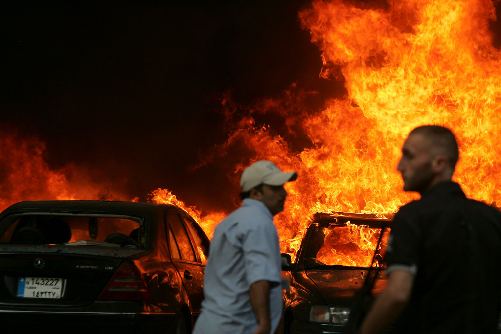 . Men gather at the site of an explosion in Beirut\'s southern suburbs July 9, 2013.  REUTERS/Issam Kobeisy