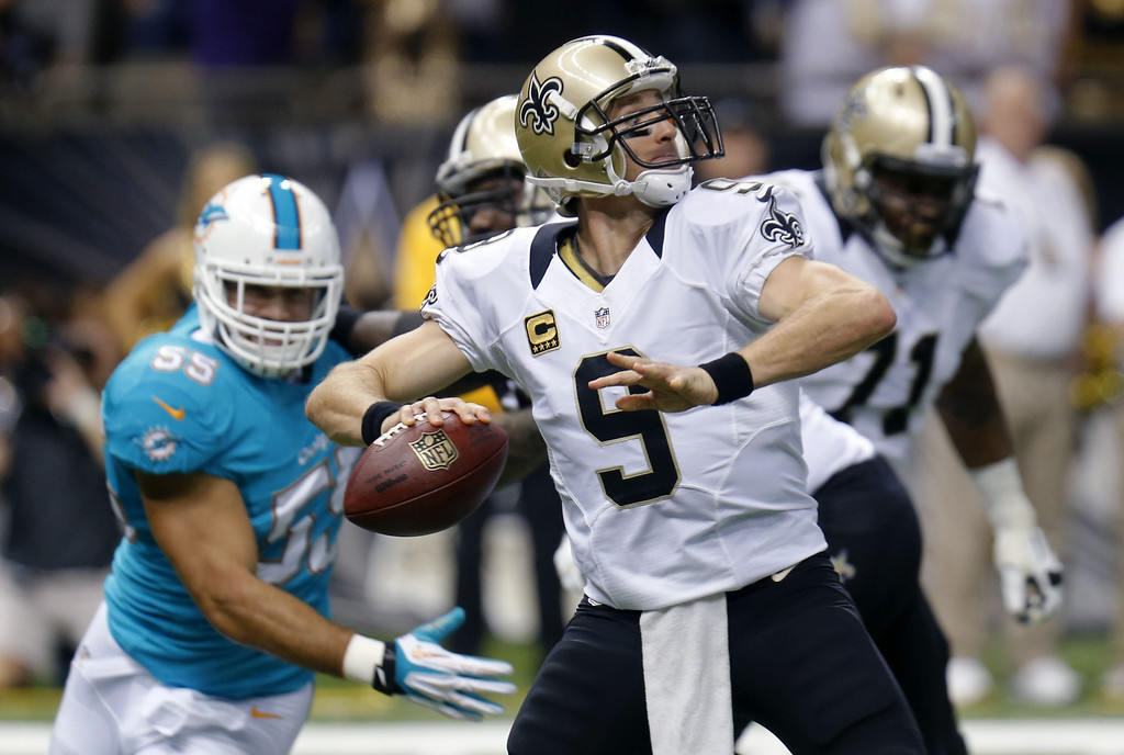 . New Orleans Saints quarterback Drew Brees (9) passes as Miami Dolphins outside linebacker Koa Misi (55) rushes in the first half of an NFL football game in New Orleans, Monday, Sept. 30, 2013. (AP Photo/Bill Haber)