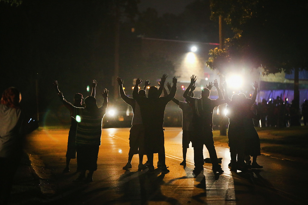 . With their hands raised, residents gather at a police line as the neighborhood is locked down following skirmishes on August 11, 2014 in Ferguson, Missouri. Police responded with tear gas as residents and their supporters protested the shooting by police of an unarmed black teenager named Michael Brown who was killed Saturday in this suburban St. Louis community. Yesterday 32 arrests were made after protests turned into rioting and looting in Ferguson.  (Photo by Scott Olson/Getty Images)