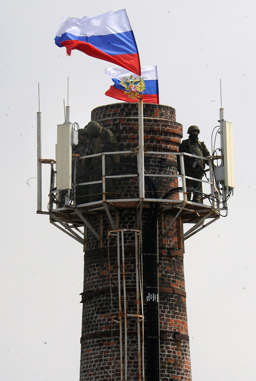 . A Russian soldier patrols on a chimney with Russian flags at the Ukrainian navy headquarters in the Crimean city of Sevastopol on March 19, 2014.  AFP PHOTO/  VIKTOR DRACHEV/AFP/Getty Images