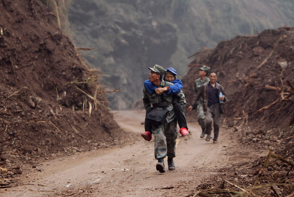 . Zhang Bin, a Chinese People\'s Liberation Army soldier carrying a 60-year-old survivor, looks up the mountainside as he makes his way down a stretch of the road to Lingguan township, which was recently cleared of debris from landslides caused by Saturday\'s earthquake, in Baoxing county in Ya\'an, Sichuan province April 22, 2013. REUTERS/Jason Lee