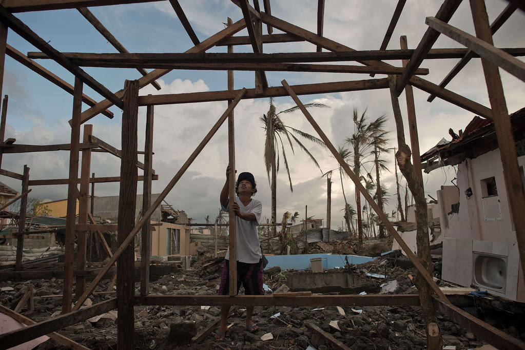 . A typhoon victim constructs his new home in Palo on November 21, 2013.  AFP PHOTO/ Nicolas ASFOURI/AFP/Getty Images