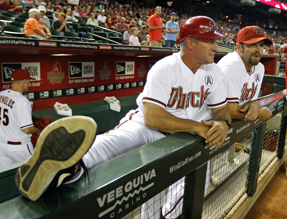 . Arizona Diamondbacks first base coach Steve Sax stretches his legs next to pitcher Heath Bell (R) before the start of their MLB Opening Day National League baseball game against the St. Louis Cardinals in Phoenix, Arizona April 1, 2013. REUTERS/Ralph D. Freso