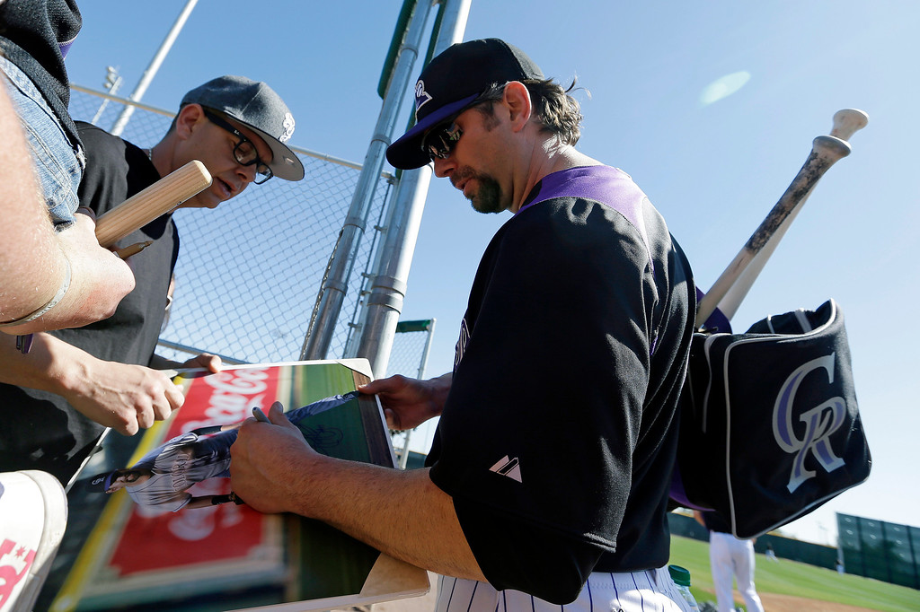 . Colorado Rockies\' Todd Helton signs autographs for fans during a spring training baseball workout Sunday, Feb. 17, 2013, in Scottsdale, Ariz. (AP Photo/Darron Cummings)