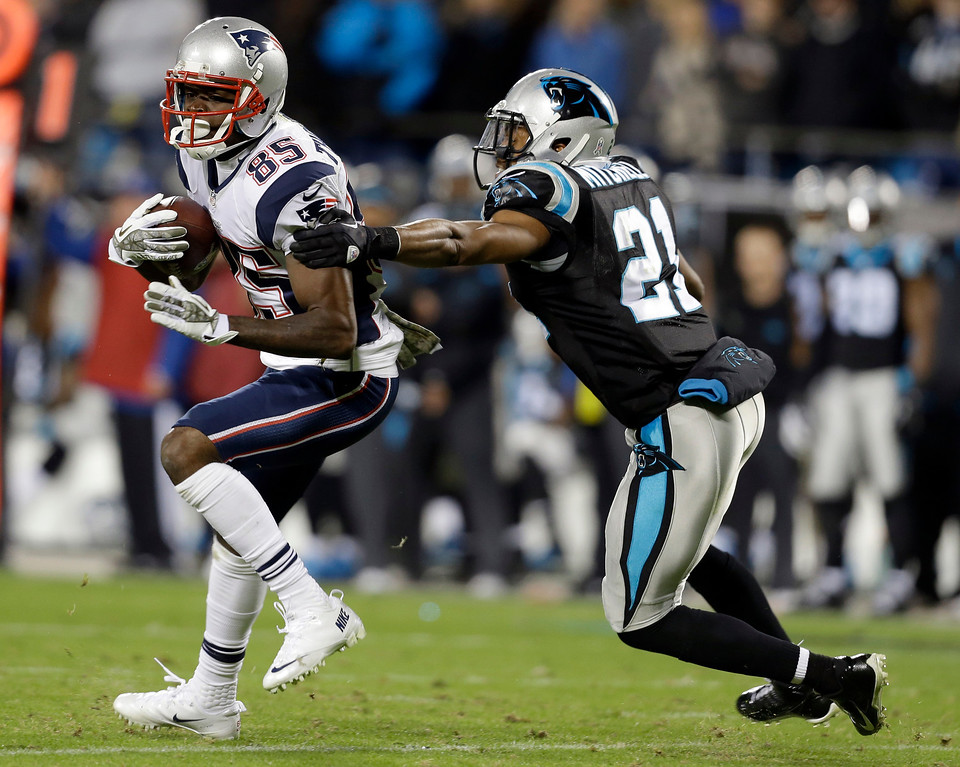 . New England Patriots\' Kenbrell Thompkins (85) runs after a catch as Carolina Panthers\' Mike Mitchell (21) defends during the second half of an NFL football game in Charlotte, N.C., Monday, Nov. 18, 2013. (AP Photo/Gerry Broome)