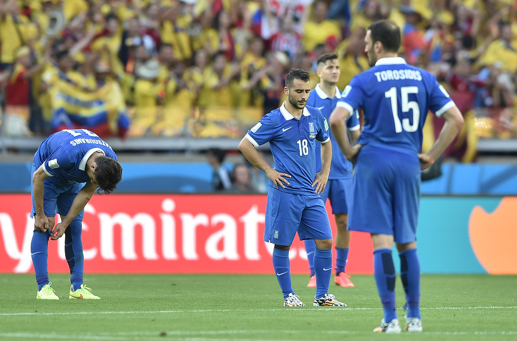 . Greece\'s forward Ioannis Fetfatzidis (2nd L) and Greece\'s defender Vasilis Torosidis (R) gesture after conceding a third goal during a group C football match between Colombia and Greece at the Mineirao Arena in Belo Horizonte during the 2014 FIFA World Cup on June 14, 2014.   AFP PHOTO / ARIS MESSINIS