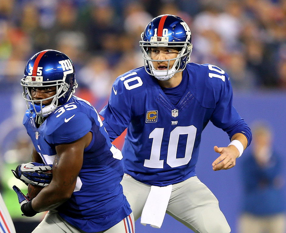 . Eli Manning #10 of the New York Giants hands the ball off to teammate  Andre Brown #35 in the first quarter against the Green Bay Packers at MetLife Stadium on November 17, 2013 in East Rutherford, New Jersey.  (Photo by Elsa/Getty Images)